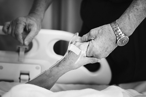 Photograph of patient holding hands with relative