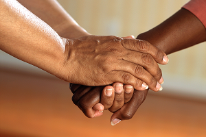 Photograph of two people holding hands