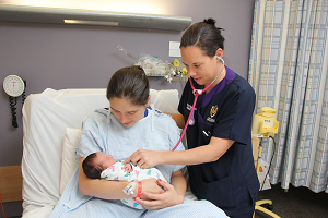 Photograph of nurse with patient and baby